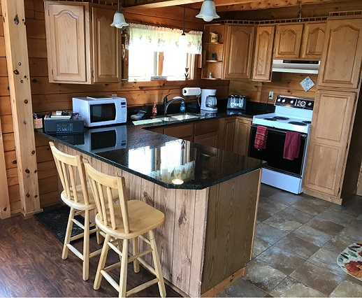 Log Cabin kitchen with shiny counter, stove, microwave and two barstools